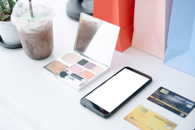 Mockup di caffè bianco tavolo bianco con mobile e carta di credito Psd Premium