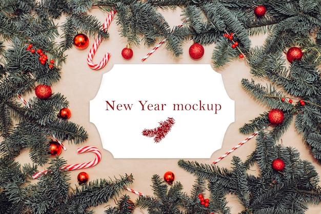 Mockup di natale, cartolina sul tavolo con rami di abete, palline rosse, bacche e bastoncini di zucchero Psd Premium