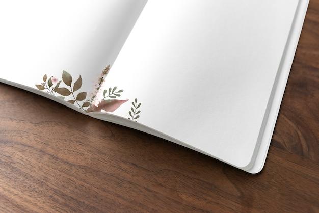 Mockup di notebook floreale su un tavolo di legno Psd Gratuite