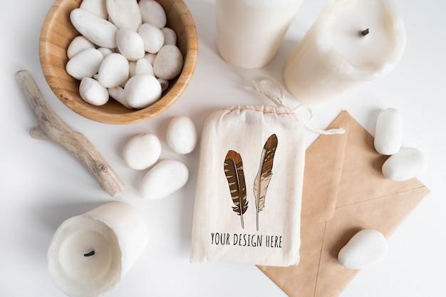 Mockup di sacchetto di cotone o marsupio e ciotola con ciottoli bianchi e boho elementi sul tavolo bianco. Psd Premium