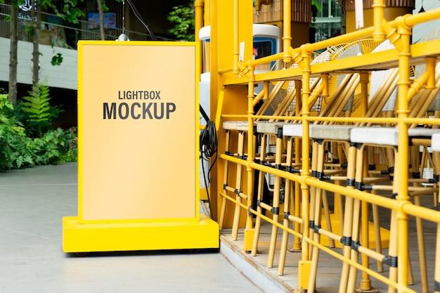 Mockup di scatola di luce gialla in una città per i tuoi contenuti pubblicitari o promozionali. Psd Premium