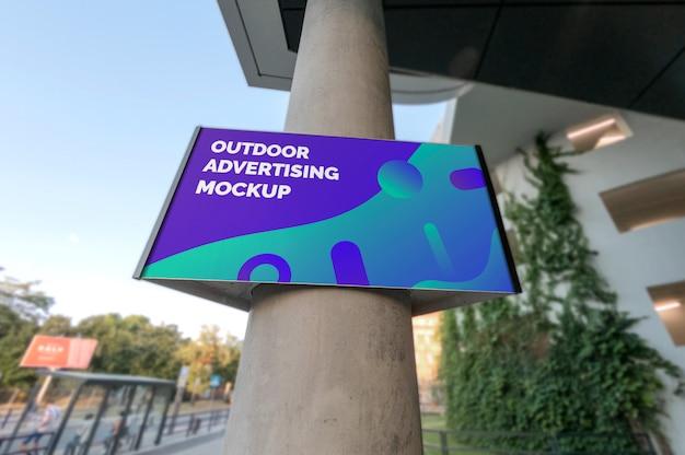 Mockup di segnaletica pubblicitaria paesaggio all'aperto appeso sulla colonna Psd Premium