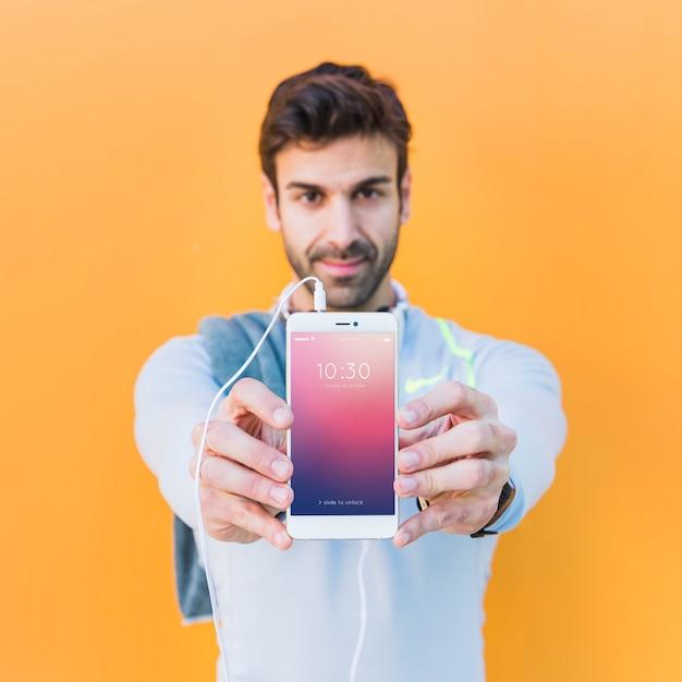 Mockup de fitness con hombre enseñando smartphone PSD gratuito