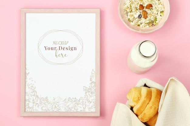 Mockup foto frame op roze achtergrond met muesli, croissant en een fles melk Premium Psd