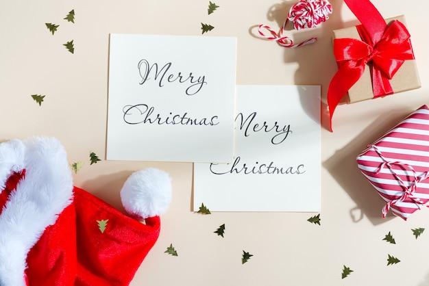 Mockup kerstkaarten met rode hoed en geschenkdozen. Premium Psd