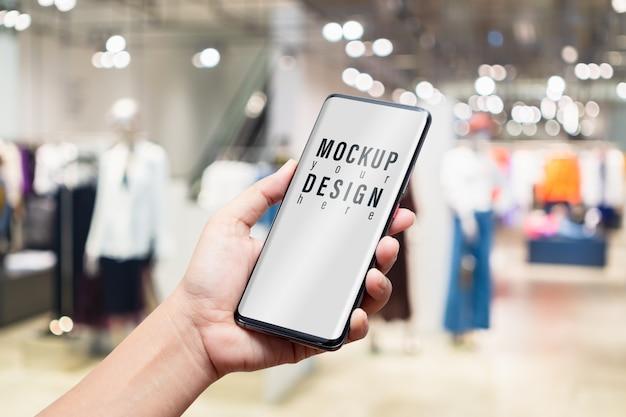 Mockup mobiele telefoon in vrouwen kleding mode winkel. Premium Psd
