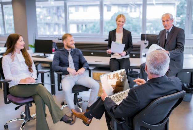 Mockup de portátil en reunión de negocios PSD gratuito
