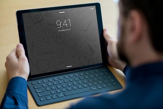 Mockup de tableta con teclado y hombre PSD gratuito