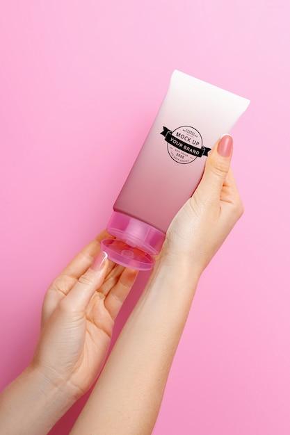 Mockup tube crème in handen op een roze ruimte Premium Psd
