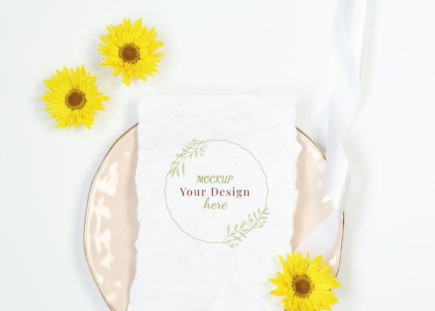 Mockup uitnodigingskaart op roze plaat met gele bloemen Premium Psd