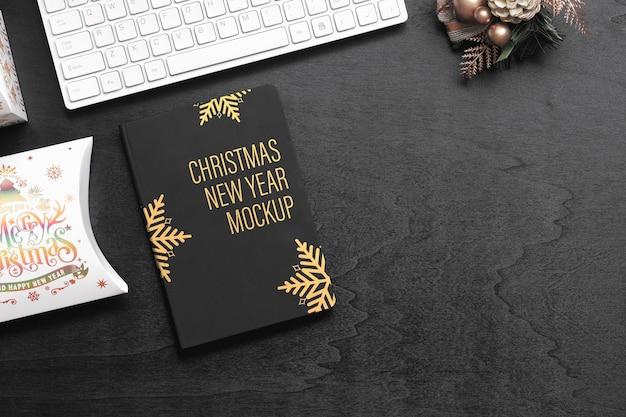 Mockup zwart kaft notitieboekje op zwart hout voor kerstmis nieuwjaar Premium Psd