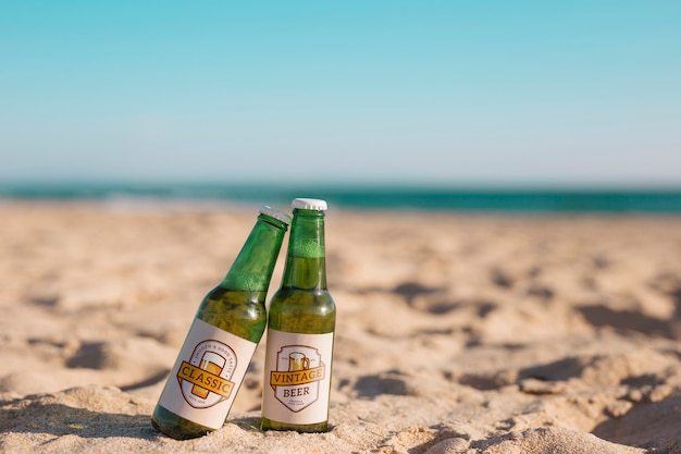 Model twee bierflessen op het strand Gratis Psd