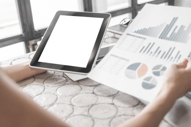 Model van dichte omhooggaande bedrijfsvrouw die met tablet en documenten in bureau werken Premium Psd