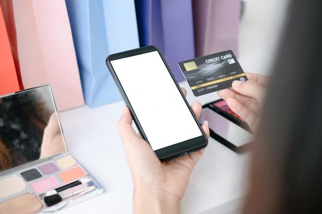 Modello di bella donna che tiene la carta di credito che compera online con lo smartphone sui siti web online Psd Premium