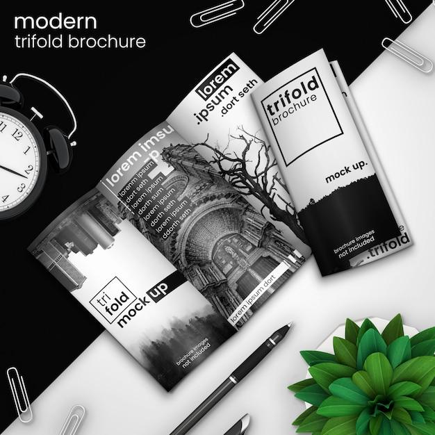 Modello di brochure a tre ante creativo e moderno di due brochure a tre ante su design moderno in bianco e nero con sveglia, graffette, penna e pianta verde, psd mock up Psd Premium