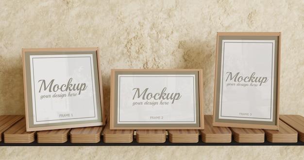 Modello di cornice a tre poster con dimensioni diverse sulla mensola a muro Psd Premium