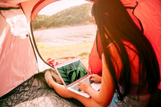 Modello di laptop con il campeggio nel concetto di natura Psd Gratuite