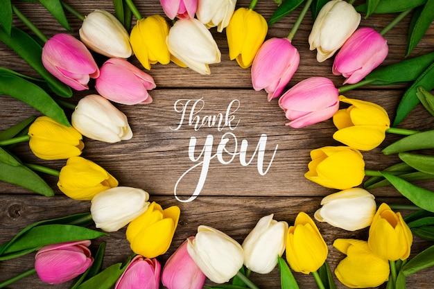 Modello di saluto con tulipani su uno sfondo di legno Psd Gratuite