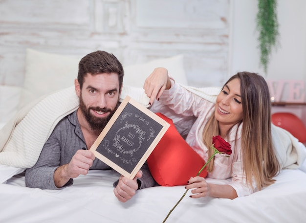 Modello di san valentino con coppia a letto mostrando ardesia Psd Gratuite