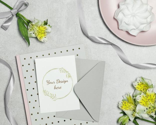 Modelprentbriefkaar op grijze achtergrond met bloemen, cake en lint Premium Psd