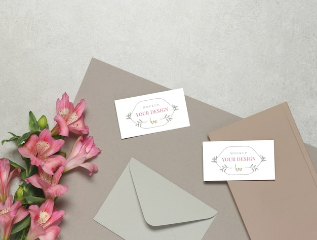 Modelvisitekaartje op grijze achtergrond, verse bloemen, grijze envelop en roze nota's Premium Psd