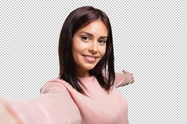 Mujer bonita joven que sonríe y feliz, tomando un selfie, sosteniendo la cámara PSD Premium