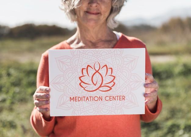 Mujer con un cartel de logotipo del centro de meditación PSD gratuito