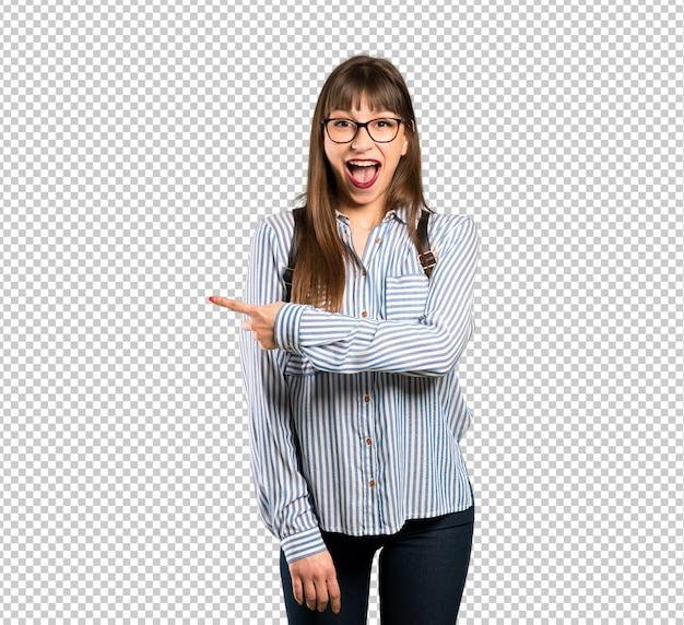 Mujer con gafas sorprendida y apuntando al costado PSD Premium