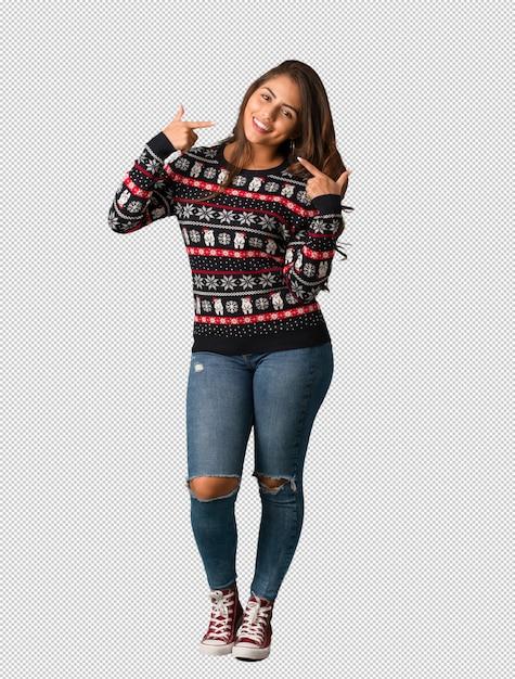 Mujer joven de cuerpo completo vestida con un jersey de navidad sonríe, señalando boca PSD Premium