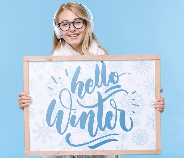 Mujer joven sonriente con cartel de maqueta PSD gratuito