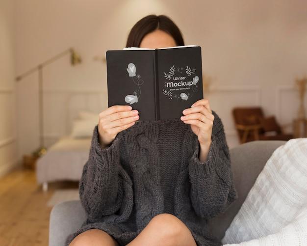 Mujer joven sosteniendo una maqueta de libro PSD gratuito