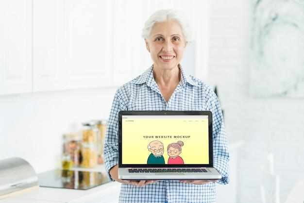 Mujer mayor sujetando mockup de portátil PSD gratuito
