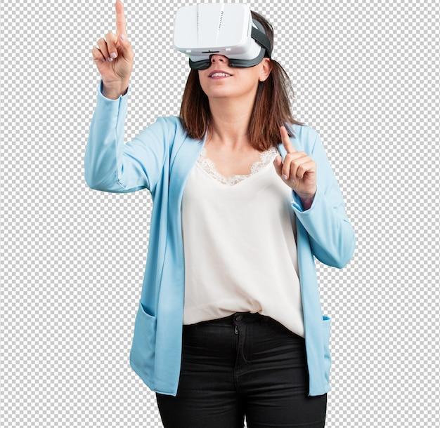 Mujer de mediana edad emocionada y entretenida, jugando con gafas de realidad virtual. PSD Premium