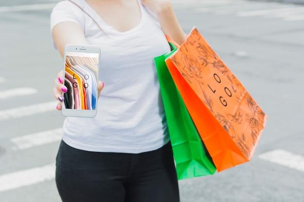Mujer con mockup de smartphone y bolsas de compra PSD gratuito