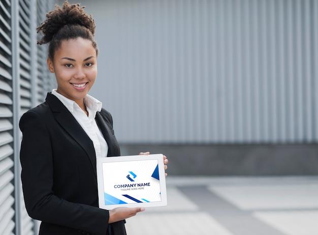 Mujer de negocios sonriente que sostiene la maqueta de la tableta PSD gratuito