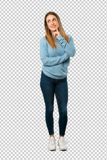 Mujer rubia con camisa azul pensando una idea mientras mira hacia arriba PSD Premium
