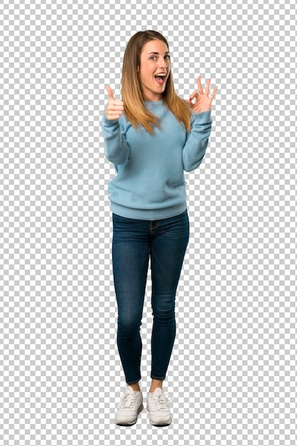 Mujer rubia con la camisa azul que muestra la muestra aceptable con y que da un pulgar encima del gesto PSD Premium
