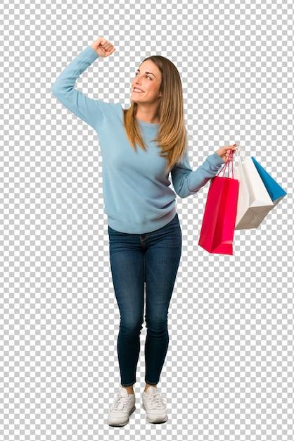 Mujer rubia con la camisa azul que sostiene muchos bolsos de compras en la posición de la victoria PSD Premium