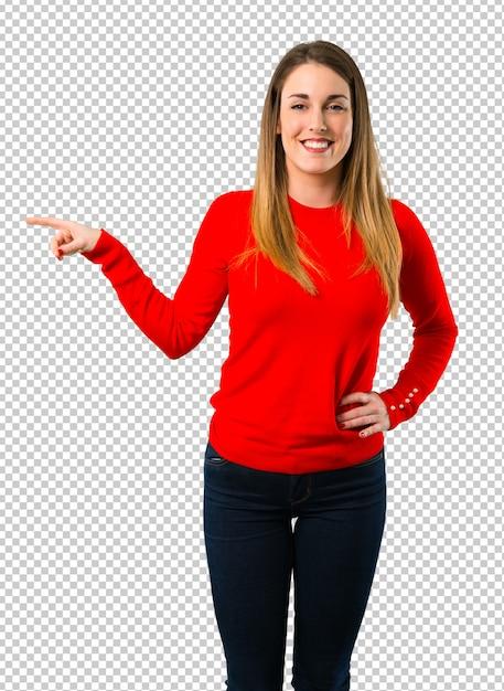 Mujer rubia joven que señala el dedo al lado y presenta un producto PSD Premium