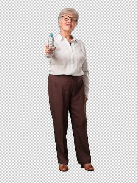 Mujer senior de cuerpo completo sonriendo satisfecha, sosteniendo una botella de agua fría PSD Premium