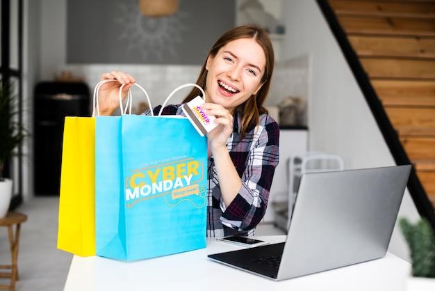 Mujer sosteniendo bolsas de papel de lunes cibernético y una tarjeta de crédito PSD gratuito