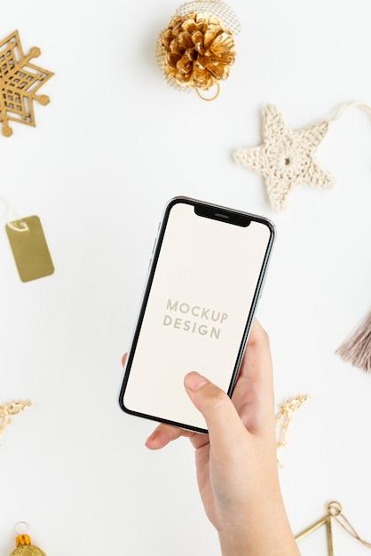 Mujer sosteniendo su teléfono sobre maqueta de adornos navideños dorados PSD gratuito