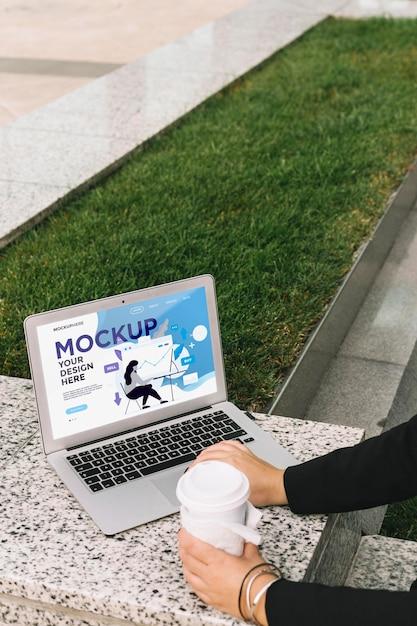 Mujer trabajando al aire libre maqueta de portátil PSD gratuito