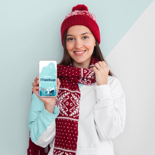 Mujer vistiendo una sudadera con capucha y sosteniendo una maqueta de teléfono PSD Premium