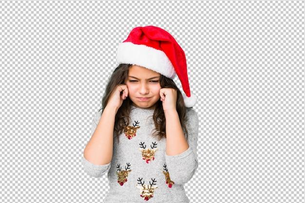 Niña celebrando el día de navidad cubriendo las orejas con las manos. PSD Premium