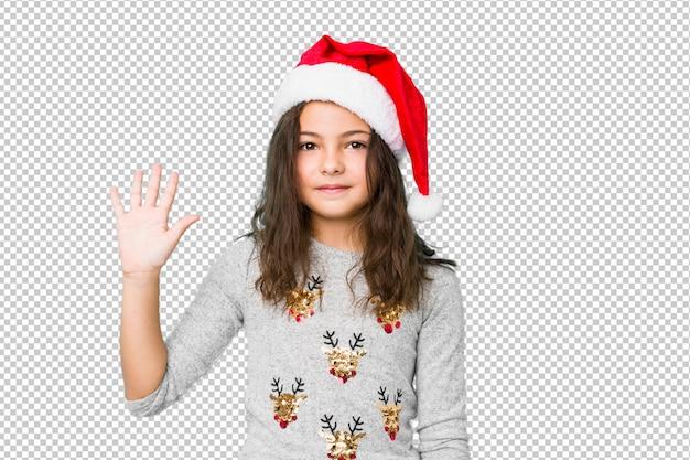 Niña celebrando el día de navidad sonriendo alegre mostrando número cinco con los dedos. PSD Premium