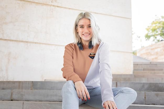 Niña sonriente con auriculares con capucha PSD gratuito