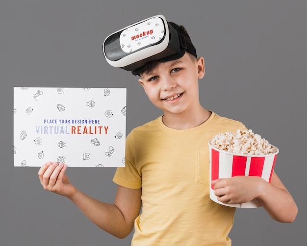 Niño con casco de realidad virtual con maqueta de tarjeta PSD gratuito