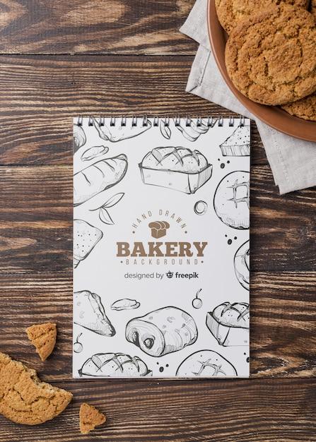 Notebook en koekjes op tafel Gratis Psd