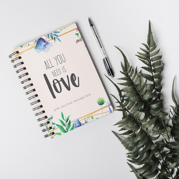 Notebook mockup naast bladeren Gratis Psd